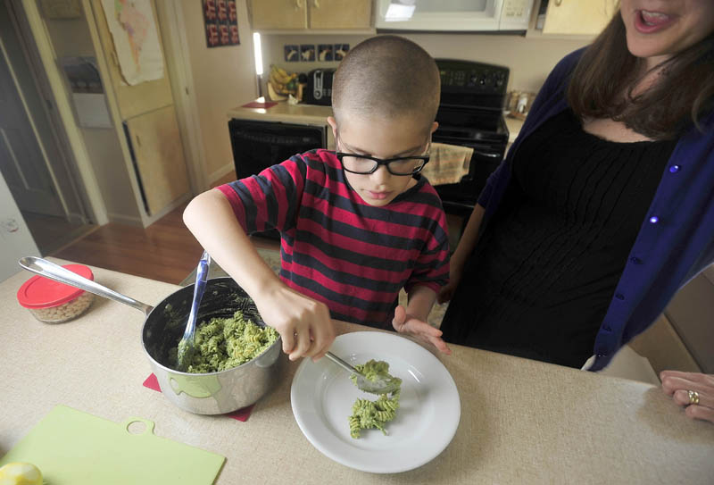 Noah Koch, 9, and his mother, Hilary, of Waterville, prepare his award-winning pesto in their Waterville home today.