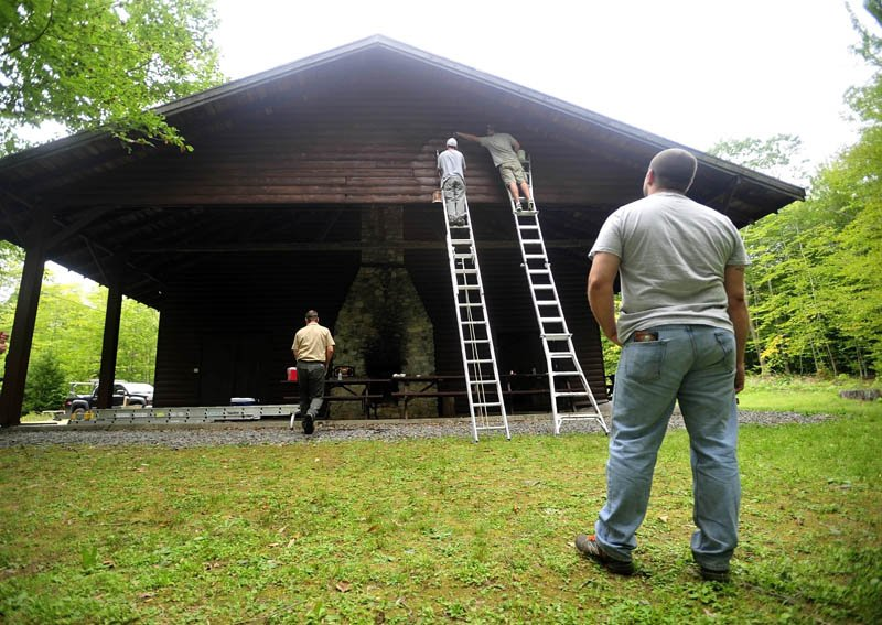 Matt Cowan, on the ladder at left, and Mat Gross, on the ladder at right, put a fresh coat of paint on the Margaret Chase Smith Hall at Lake George Regional Park on the Canaan and Skowhegan town line today as Backyard Farms coworker Matt Abbott, foreground, watches. The crew from Backyard Farms has been volunteering time at Lake George Regional Park, helping with maintenance and general upkeep of the facility.