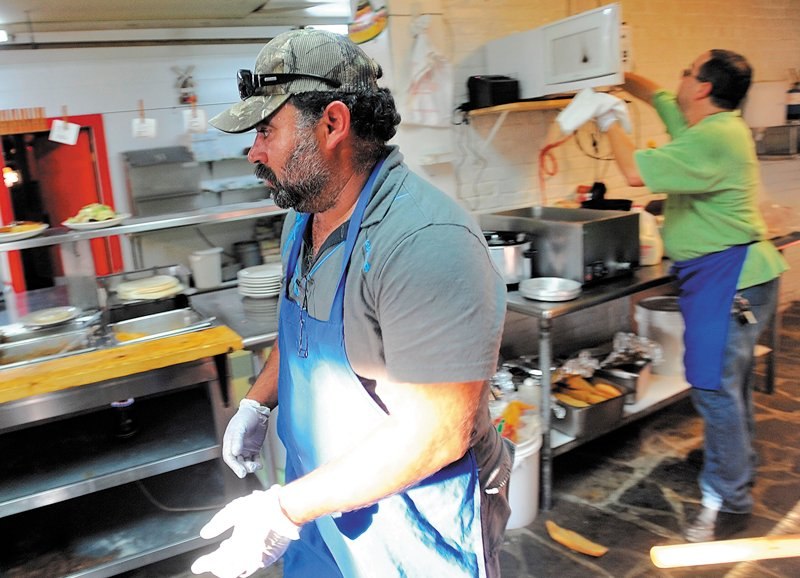 This October 2011 file photo shows Myao Perez, center, in the kitchen at Cancun Restaurant in Waterville as Hector Fuentes, back right prepares food in the background. Perez volunteered to help Fuentes keep his business open after several workers were arrested for charges of illegal immigration.