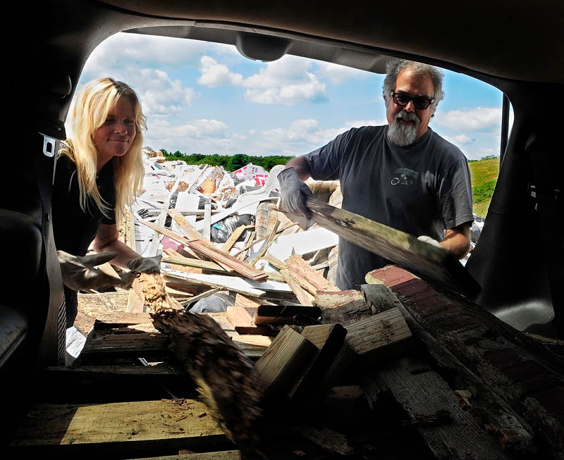 Maggie Peele, left, and Don Vellani throw scrap wood onto the large rubbish pile at Hatch Hill Landfill today in Augusta.
