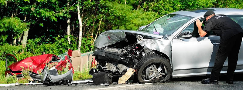 Kennebec County Sheriff's Department Sgt. Mike Pion, looks at one of the cars involved while beginning his reconstruction of an accident today on the Route 3 connector between Riverside Drive and North Belfast Avenue in Augusta.