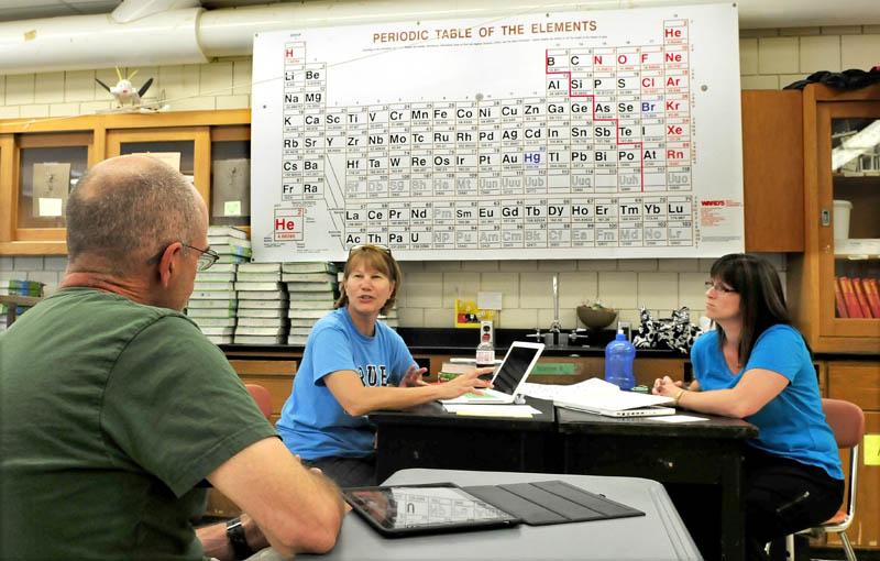 Skowhegan Area High School science teachers Scott Pillsbury, Barbara Toner and Stephani Sawyer-Main prepare curriculum for the new school year recently.