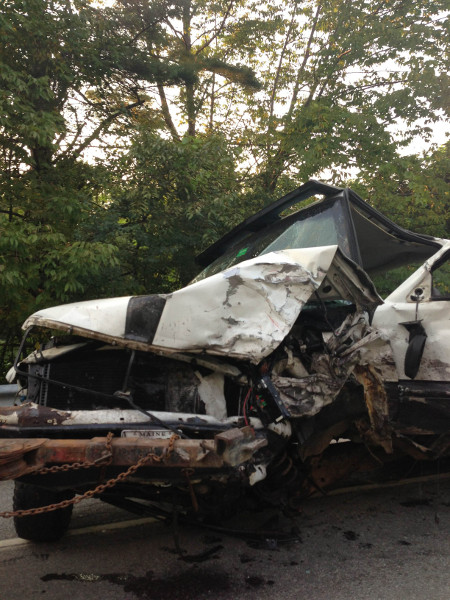 One of the two pickup trucks damaged in a double-fatal head-on collision on Riverside Drive in Vassalboro today is hooked up to a wrecker.