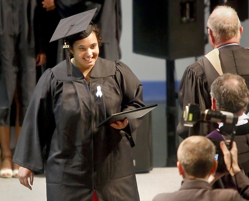 Felicity Hills, who earned her degree in mathematics and physics, walks across the stage with her diploma during the Bowdoin College commencement in May.