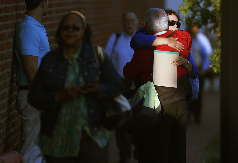 A woman hugs a man before entering the Washington Navy Yard as employees return to work Thursday. The Washington Navy Yard returned to nearly normal operations three days after it was the scene of a mass shooting in which a gunman killed 12 people.
