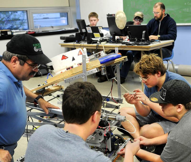 Members of the Gardiner Area High School robotics team work on their disc-shooting robot at the school in Gardiner on Sept. 10.