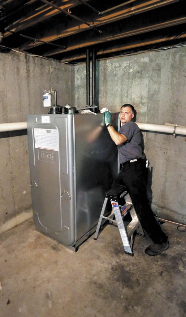 Chris Sprague, a service manager at Giroux Energy, installs a 275-gallon ROTH oil tank on Sept. 3 in the basement at a home in Gorham.