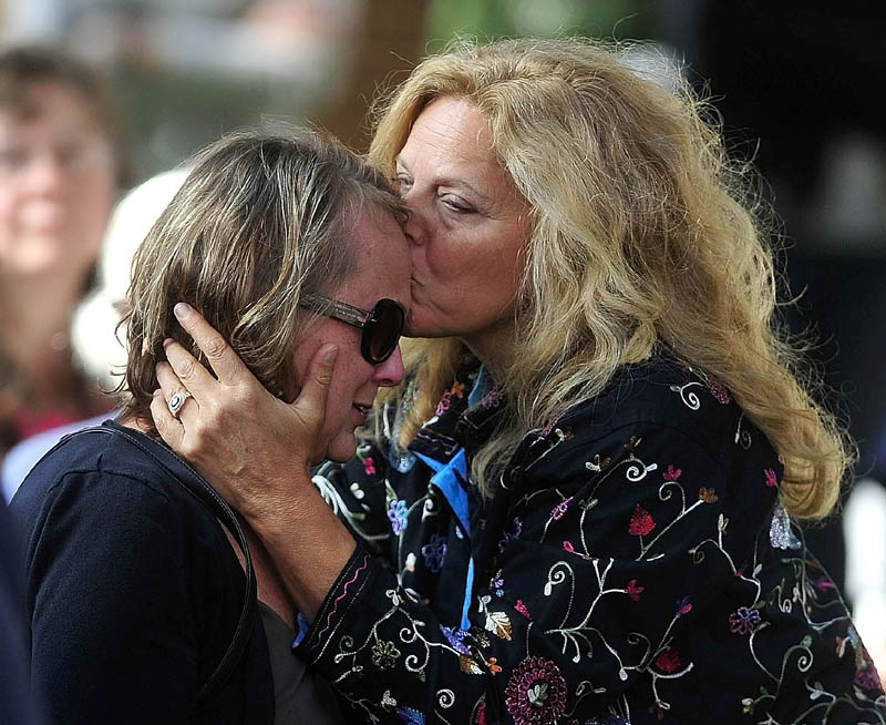 Andrea Ré, right, shares a moment with Jan Taylor during a celebration of her brother Bill Taylor's life at Castonguay Square in downtown Waterville today. More than 450 people attended to pay their respects.