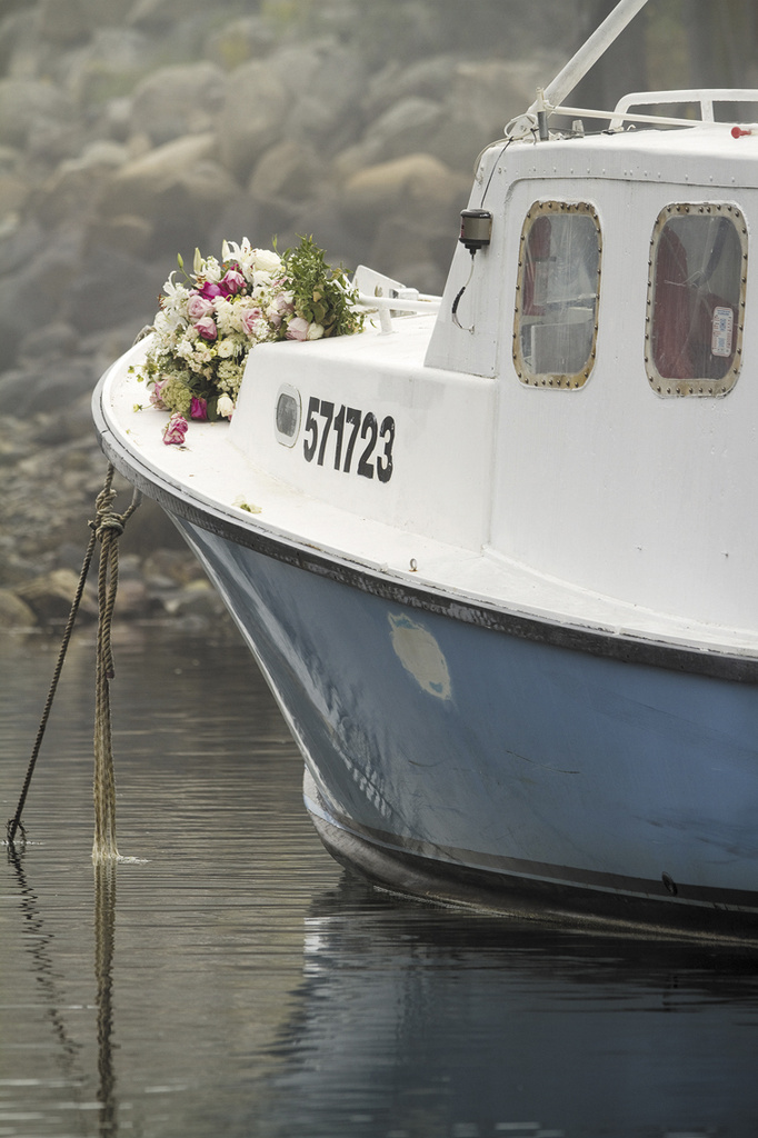 Bouquets of flowers are set on the bow of the lobster boat