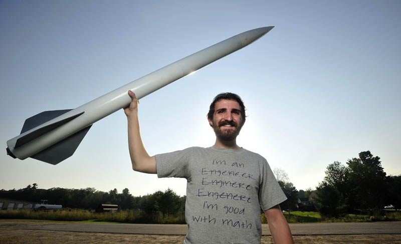 Michael Ostromecky, 22, of Winslow, and six colleagues are planning to launch an 18-foot rocket to about 180,000 feet into the atmosphere next week. He designed the five-foot rocket he is holding and it reached 2,000 feet.