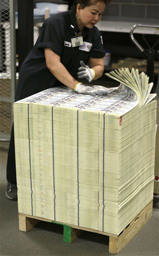 A stack of uncut sheets of $100 bills are inspected before being moved during the printing process at the Bureau of Engraving and Printing Western Currency Facility in Fort Worth, Texas.