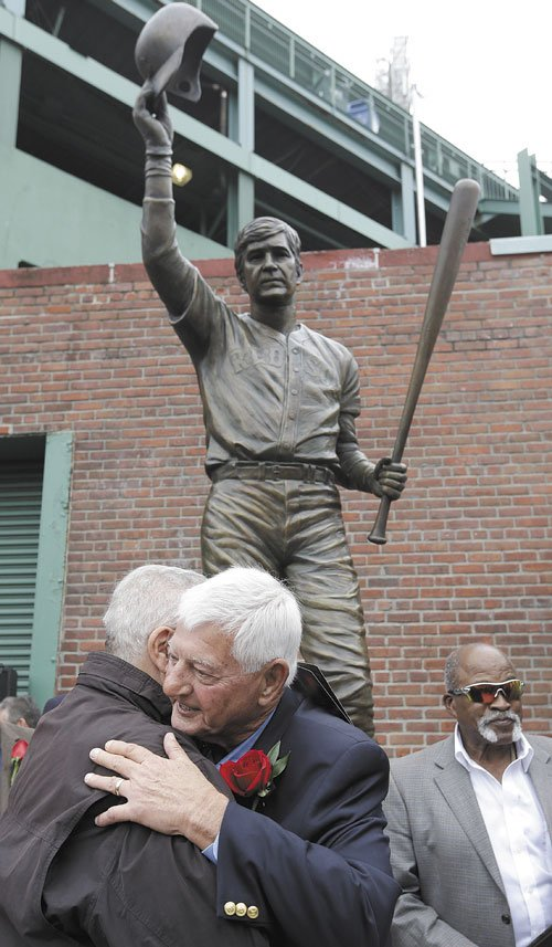 GREAT CAREER: Hall of Famer Carl Yastrzemski, center, hugs former Boston Red Sox's Ted Lepcio, left, during a ceremony held to unveil a statue of Yastrzemski on Sunday at Fenway Park in Boston. Former Red Sox's Luis Tiant stands behind right.
