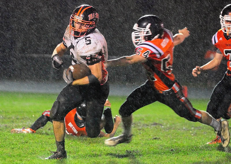Brunswick's Lucas McCue runs away from Gardiner's Walker Norton during the Dragons' 54-0 win over the Tigers on Friday at Hoch Field in Gardiner.