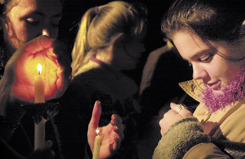 Sarah Kaminshine, right, then a Colby College senior, tries to protect her candle from the wind during a vigil outside Anthony Mitchell Schupf dormitory in memory of Dawn Rossignol on Sept. 18, 2003, in Waterville.