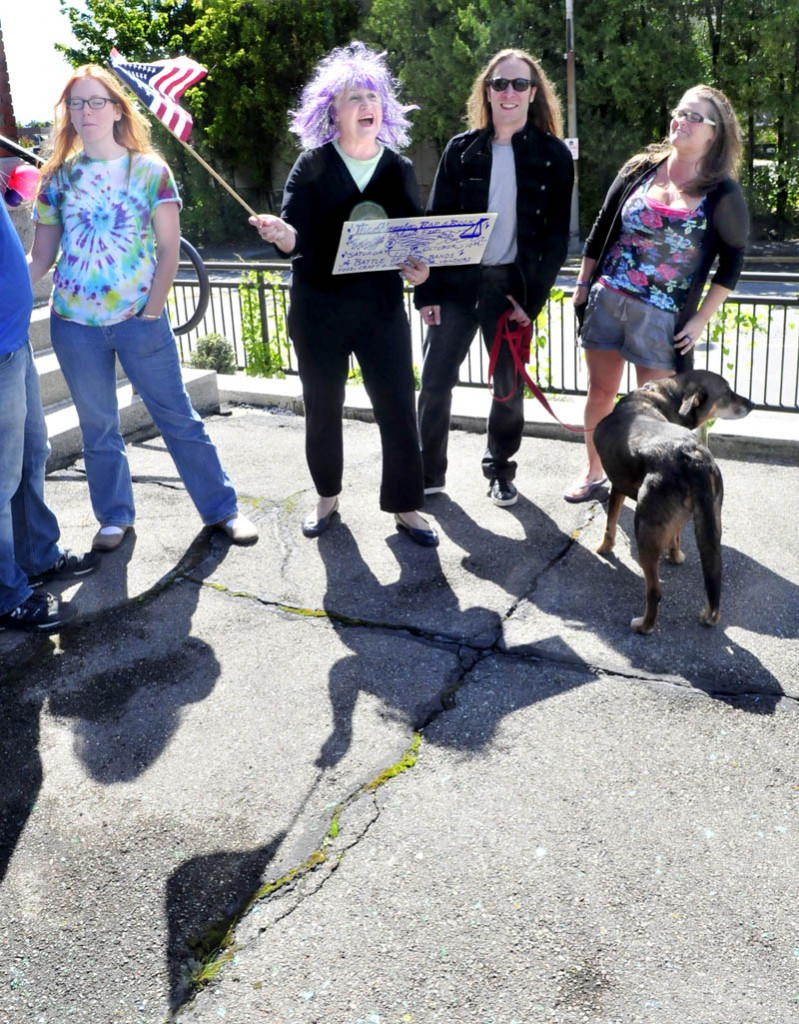 As music plays on the steps of the Waterville Public Library, Katherine Dall waves an American flag as people begin to assemble ontoday for the Peace Choir on Gaia event. Sunday was the first day of an event planned to take place for the next three Sundays at noon, to promote peace and to socialize. From left are Katie Feliciano, Dall, Josh Couture and Jade Noonan.