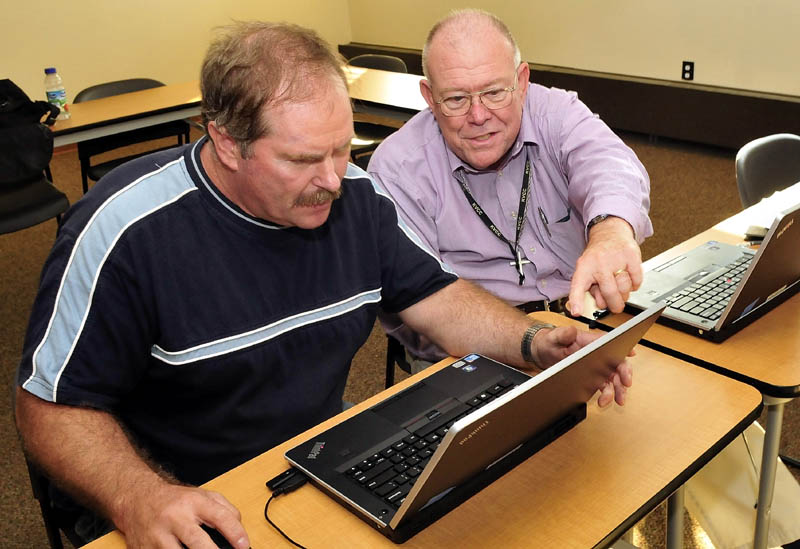 Laton Edwards, right, works with Edwin Weeks on a computer at the Waterville Public Library recently.