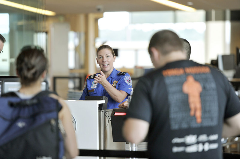TSA employee Donna Castle calls travelers to the Portland jetport's document check-in site. A Precheck program is likely to make getting through security faster even for those who aren't enrolled, by diverting some travelers out of the regular lines.