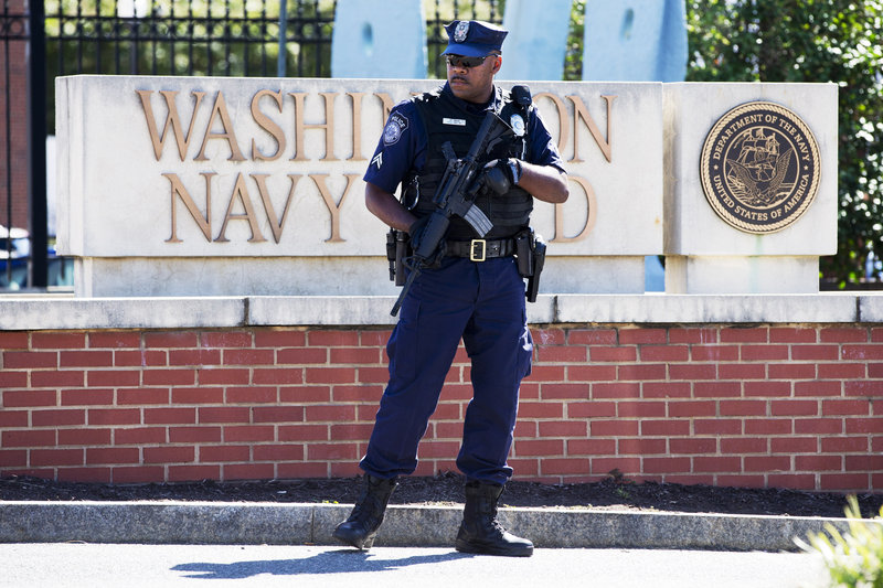 An armed officer who said he is with the Department of Defense, works near the gate at the Washington Navy Yard, closed to all but essential personnel, in Washington, on Tuesday, Sept. 17, 2013, the day after a gunman launched an attack inside the Washington Navy Yard on Monday, spraying gunfire on office workers in the cafeteria and in the hallways at the heavily secured military installation in the heart of the nation's capital. (AP Photo/Jacquelyn Martin)
