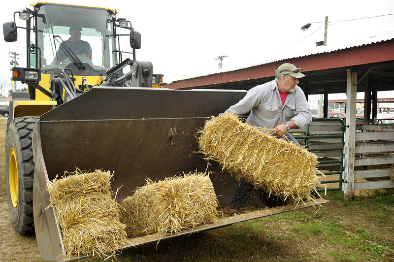 Fair worker Mike Haskell of Windham tosses bales of hay into stalls awaiting the animals' arrival. Fellow fair worker Steve Googins of Gray is manning the front-end loader.