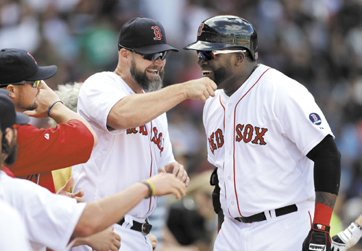 STILL ROLLING: Boston's designated hitter David Ortiz, right, is welcomed to the dugout by David Ross, center left, after Ortiz hit a home run during the Red Sox' 5-2 win over Toronto on Sunday in Boston. The Red Sox aved wrapped up the AL East title and won't play their first playoff game for nearly two weeks, but continue to try to win.