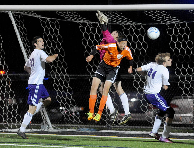 Waterville Senior High School goalie Liam Edwards, tries to punch the ball away from the net as Winslow High School's Logan Vachon, 6, tries to head the ball in the goal in the first overtime in Class B soccer action Tuesday at Thomas College in Waterville. Waterville and Winslow tied 0-0 in double overtime.