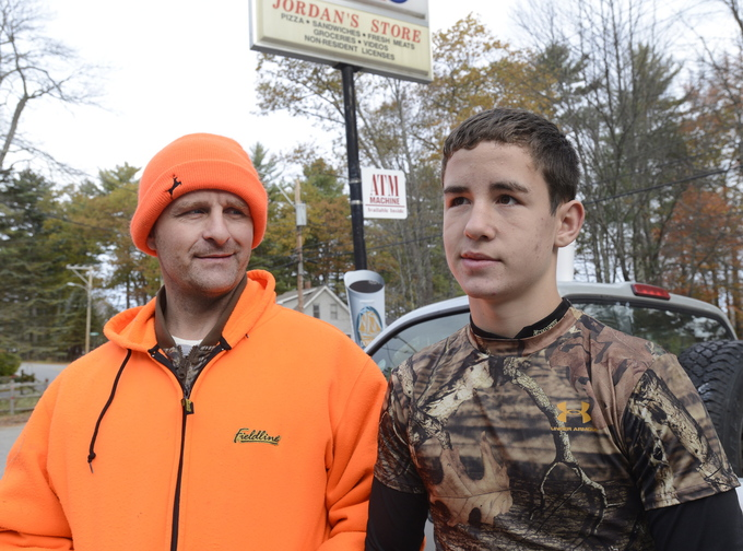 Joseph Kenney, right, and his dad, Joe Kenney, take a break from hunting on Saturday, at Jordan's Store in Sebago.