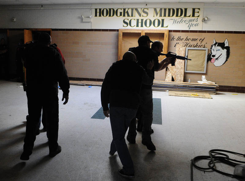 Augusta firefighter/paramedics crouch low as they follow Augusta police officers into a simulated school shooting incident Friday at the former Hodgkins middle school in Augusta.