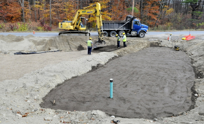 COVERED: Workers with Manter Construction cover a filtration system in Skowhegan on Monday. The system will help remove contaminated runoff water and will benefit the trout population in Whitten Brook.