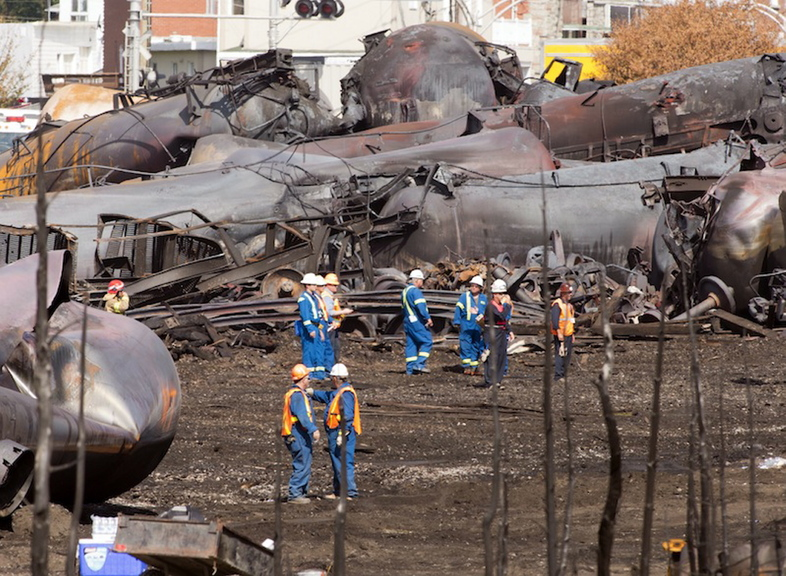 Workers stand before mangled tanker cars Tuesday, July 16 at the crash site of the train derailment and fire in Lac-Megantic, Quebec. The July 6 accident left 47 people dead.