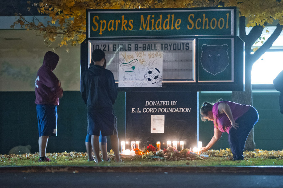 Community members gather to pay their respects to Michael Landsberry, a 45-year-old eighth-grade math teacher, soccer coach and former Marine who was killed by an eighth-grader at Sparks Middle School on Monday, Oct. 21, 2013 in Sparks, Nev. The 12-year-old student who opened fire on the middle school campus, wounding two classmates and killing Landsberry, before he turned the gun on himself, got the weapon from his home, authorities said Tuesday. School District police said they are still working to determine how the boy obtained the 9mm semi-automatic Ruger handgun used in the Monday morning spree at Sparks Middle School. The boy's parents are cooperating with authorities and could face charges in the case, police said.