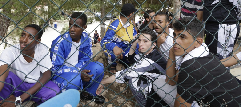 Migrants answer a reporter's questions at a temporary camp at the Italian island of Lampedusa on Friday. A ship carrying African migrants toward Italy caught fire and capsized off the Sicilian island Thursday, spilling hundreds of passengers into the sea, officials said.
