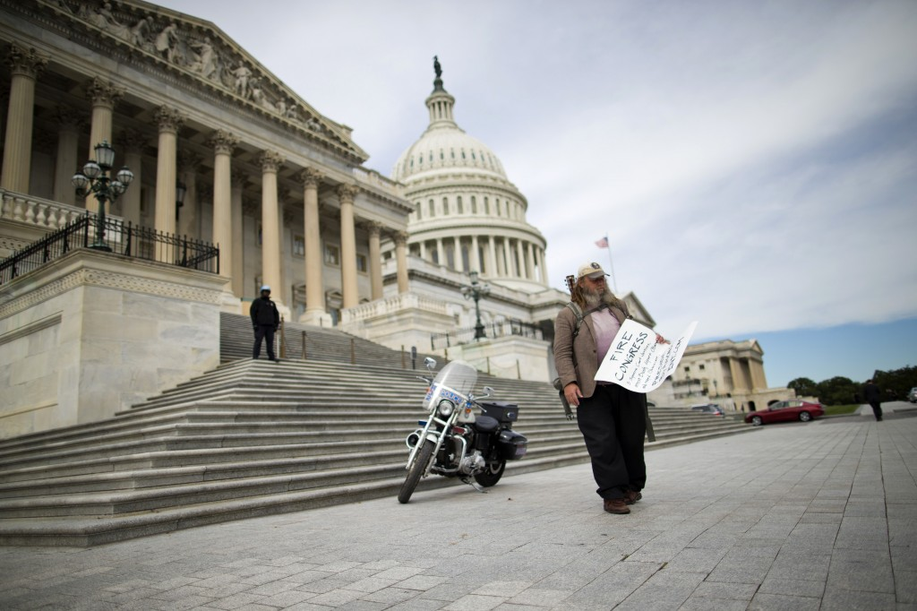 """Rick Hohensee of Washington holds a """"Fire Congress"""" sign Tuesday near the House steps on Capitol Hill in Washington during the second week of the partial government shutdown."""