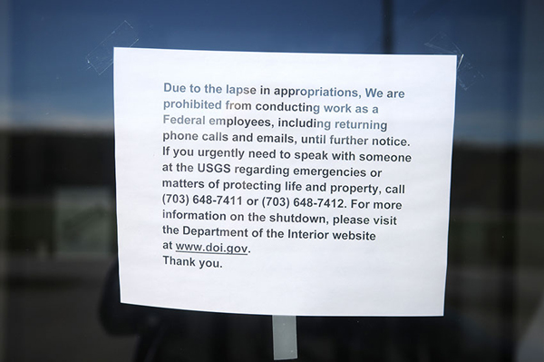 A paper sign describing the government shutdown hangs on the entrance of the U.S. Geological Service building on Whitten Road in Hallowell.