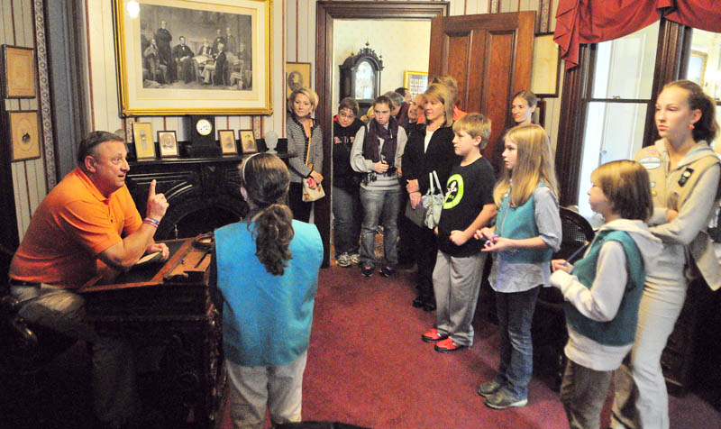 Gov. Paul LePage talks sits at James Blaine's senatorial desk in the Blaine Study while leading a tour for people who donated to a food drive on Saturday at the Blaine House in Augusta. He told the visitors about Blaine who lived in the house, that is now Governor's mansion at the corner of State and Capital Streets. Besides being a Senator, Blaine was Speaker of the House, an 1884 Republican presidential candidate, US Secretary of State and part-owner of the Kennebec Journal.