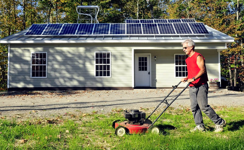 Mike Grant mows the lawn in front of the solar-powered Habitat for Humanity home recently completed on Jacques Lane in Oakland on Thursday. There will be an open house event this Sunday from 1 to 3 p.m.