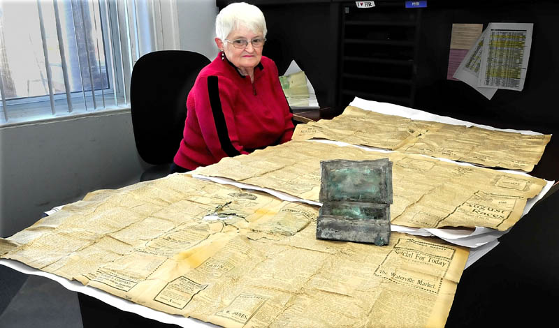 Trudy Lovely, superintendent of the Pine Grove cemetary in Waterville, displays a small box that contained a penny, pen and four 1907 Morning Sentinel newspaper pages that was found by workers tucked away in a time capsule near a corner stone at the cemetary chapel.