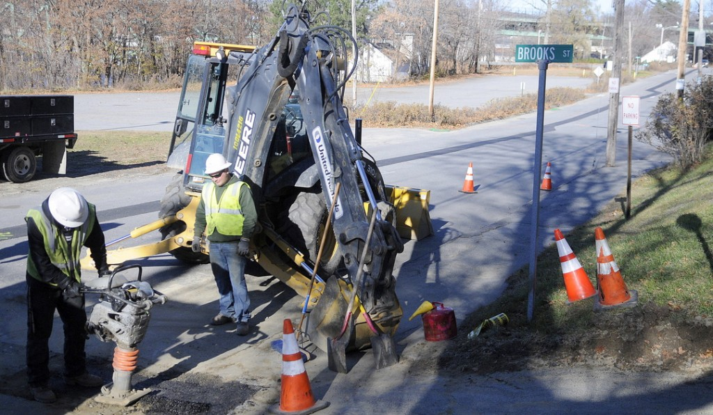 PATCHING: Tetra Tech employees Chad Kemp, left, and Tyler Frost patch Arsenal Street in Augusta on Wednesday after crews repaired a Summit Natural Gas pipeline that leaked air the night before.