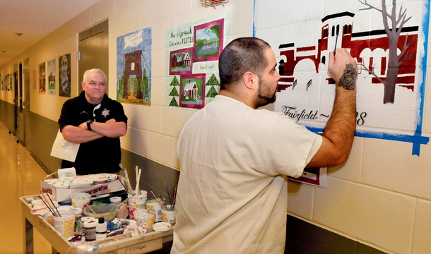 LOCAL POSTCARDS: Somerset County Jail inmate Leo Coutu adds color to one of 28 images from the Somerset Bicentennial quilt of area town landscapes on the walls at the Madison facility on Wednesday. Watching is Compliance Officer Sean Maguire. Plans are underway to transfer the scenes into postcards as part of a prison industry.