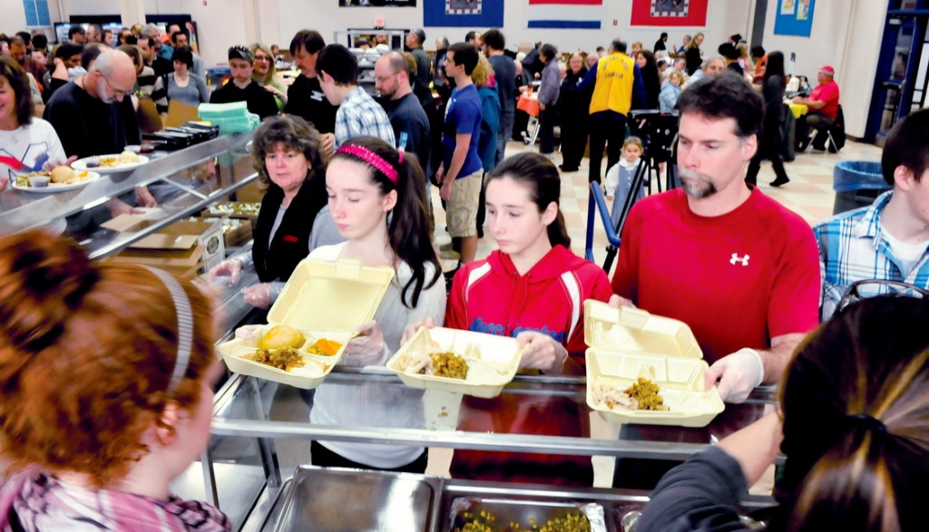HELPING OTHERS: The Vigue family pitched in to serve dinners during the 24rd annual Messalonskee Thanksgiving Day Community Meal in Oakland today. In photo from left Julia, Kaitlyn and father Jeremy Vigue fill plates of food from volunteers for the hundreds of area folks who ate and mingled with other diners.