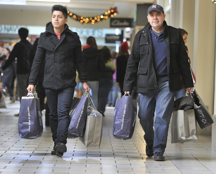 Jorge Jurado and his son Jorge Jurado Jr., visiting from New Jersey, carry their purchases out of the Maine Mall in South Portland after a morning of shopping on Black Friday. Southern Maine retailers reported brisk sales and steady crowds.
