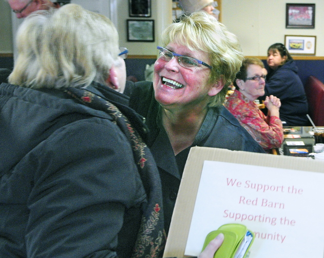Barn fan: Owner Laura Benedict, right, hugs Carol Foreman, of South China, after Foreman brought a sign supporting The Red Barn on Saturday in the restaurant's main room in Augusta.