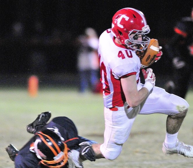 Staff photo by Joe Phelan Cony wide receiver Jonathan Saban is tripped up Brunswick's Pearson Cost, left during a game on Friday November 15, 2013 in Bath.
