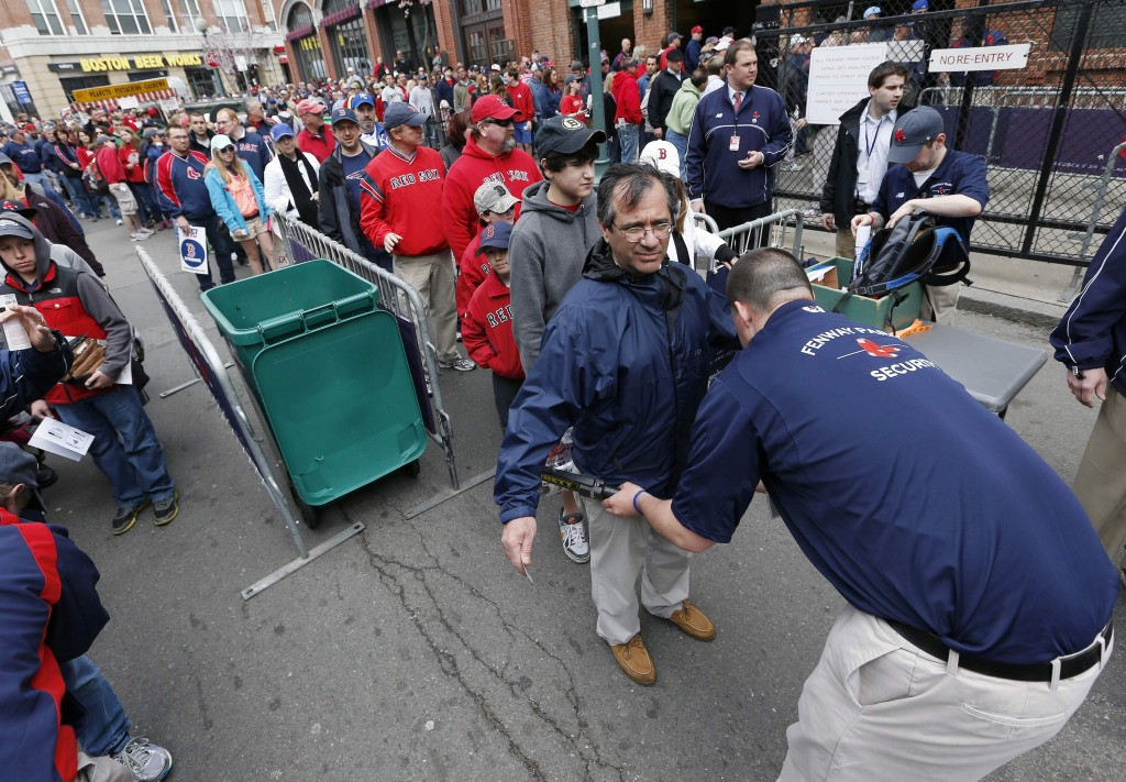 In this April 20, 2013 file photo, fans pass through a security checkpoint before entering Fenway Park for a baseball game between the Boston Red Sox and the Kansas City Royals in Boston. Baseball fans should expect to go through a metal detector to see their team play in 2014. MLB security director John Skinner says at a panel discussion at Harvard that the commissioner's office plans to recommend walkthrough metal detectors.