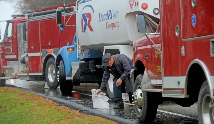 Shawn Mullen, 46, a delivery driver for Dead River Oil, mops up spilled fuel in front of 256 Belgrade Road in Oakland on Friday. The delivery truck apparently spilled small amounts of oil for about six miles in Oakland while making deliveries, according to a town fire official.