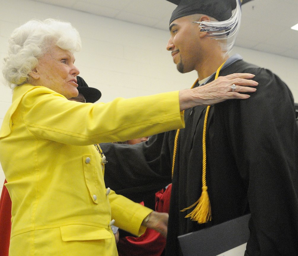 Accomplishment: Maine State Prison inmate Sergio Hairston hugs philanthropist Doris Buffett on Monday after he received his diploma from the University of Maine at Augusta during a graduation ceremony at the prison in Warren. A total of 14 men incarcerated at the prison received diplomas. Buffett, the sister of legendary investor Warren Buffett, founded the Sunshine Lady Foundation that supports educating inmates across the United States.
