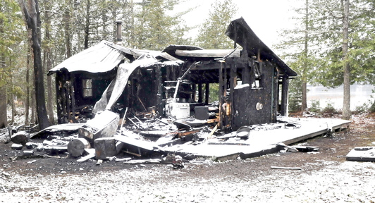 GONE: The contrast between the snow and blackened remains of a camp can be seen on Sunday on the Ironbound Pond Road in Solon after fire destroyed the home on Saturday.