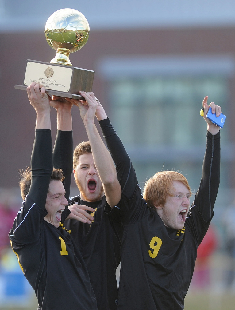 CELEBRATE: Maranacook High School captains Nick LaCasse, 10, Taylor Wilbur, 11, and Alex Tooth, 9, celebrate after receiving the state champion trophy in the Class C State Championship game at Hampden Academy on Saturday. Maranacook defatted Madawaska 2-0.
