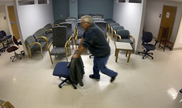 Rolling away: Mike Thomas, of Monmouth, rolls a desk chair down a hallway during the public sale of items from the former MaineGeneral Medical Center on Saturday on East Chestnut Street in Augusta.