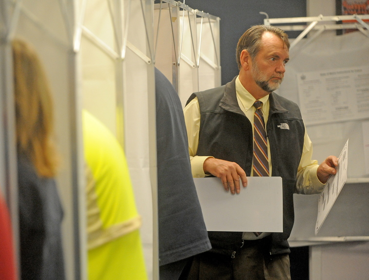 Lakefront vote: Milt Dudley, exits the voting booth after casting a ballot at the China Town Office on Tuesday. Voters turned out to decide whether to buy lakefront property and to elect town officials.
