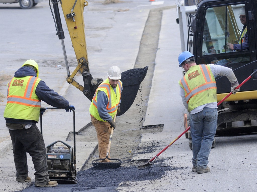 HEADWAY: Workers from McGee Construction, of West Gardiner, patch a gas pipeline trench Tuesday in Hallowell. The subcontractors are working for Summit Natural Gas of Maine laying the energy line across Central Maine.